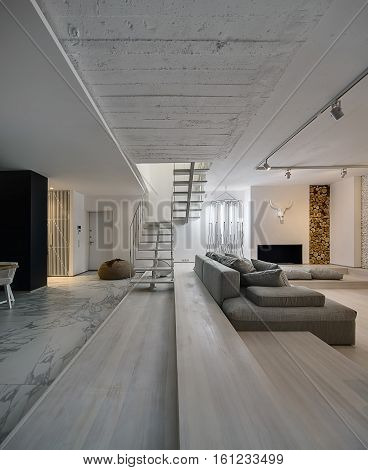 Hall in a modern style with white walls. There is a white wooden stair with a metal railing, gray sofa with pillows, glowing tube lamps, brown pouf, door, fireplace, white decorative buffalo skull.