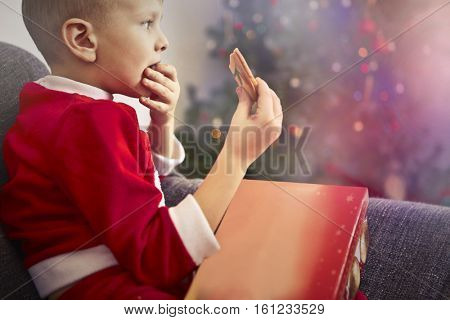 Child in Santa clothes eating Santa's cookie
