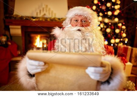 Santa Claus with a list of children wishes for Christmas gifts