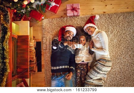 Half- cast family making Christmas selfie in lying position