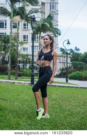 Full length shot of beautiful fitness female model in black sportswear standing on grass in city park and listening to music in earphones holding a bottle.