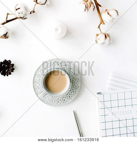 Flat lay trendy creative feminine accessories arrangement with coffee cotton branch and diary. Cotton branch notebook coffee cup fir cone on white background. Top view