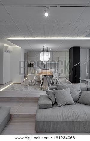Modern interior with white walls and a stair with metal railing. There is a gray sofa with pillows, kitchen zone with wooden table and chairs, glowing lamps with white lampshades. Vertical.