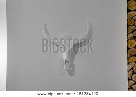 White decorative buffalo skull on the light wall. It drops shadows on the wall. On the right there are firewood. Closeup. Horizontal.
