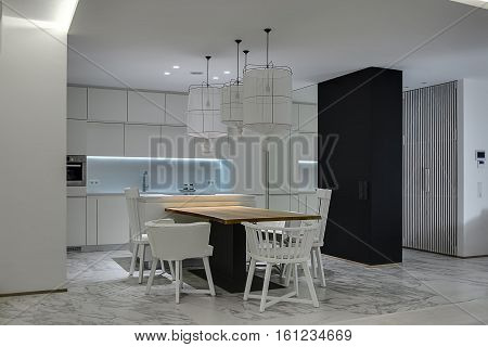 Contemporary kitchen with white walls and gray tiles with patterns on the floor. There is a wooden table with white chairs, kitchen island with a stove, white lockers, oven, sink and faucet, mirror.