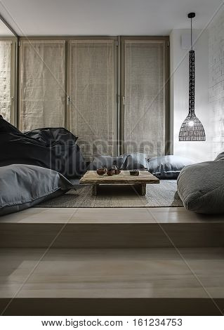 Modern room with white brick wall and a parquet. There is hanging glowing wicker lamp, tall windows, big pouf and pillows on the floor. Between them there is small wooden coffee table with cups.