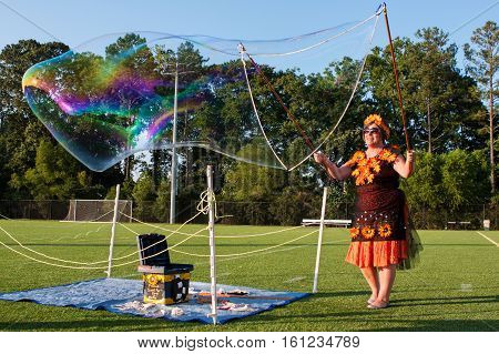 KENNESAW, GA - AUGUST 2016: A woman uses soapy water to create huge bubbles for people to enjoy at a festival in Kennesaw GA on August 27 2016.