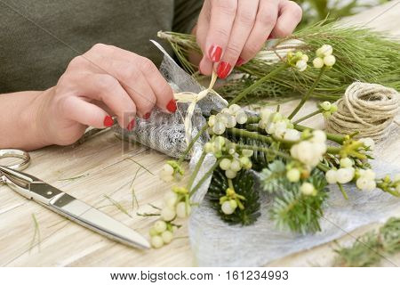 closeup of a young caucasian woman with her fingernails painted red arranging a bunch of mistletoe wrapped in a silvery fabric, on a rustic wooden surface
