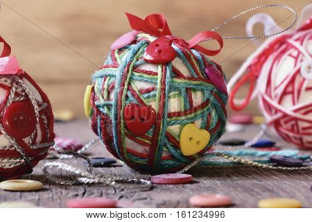 closeup of some handmade christmas balls, made with ribbon bow, strings and buttons of different colors, on a rustic wooden surface