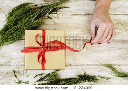 high-angle shot of a young caucasian woman with her fingernails painted red tying a red ribbon around a gift wrapped in a golden paper, on a rustic wooden surface full of natural twigs and branches