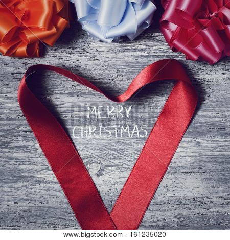 some satin gift ribbon bows of different colors and a red satin ribbon forming a heart on a rustic wooden surface and the text merry christmas in the center
