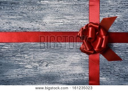 a crossed red satin ribbon tied in a gift bow on a gray rustic wooden surface, with some negative spaces