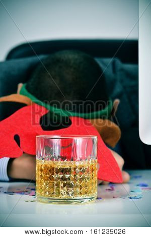 closeup of a young caucasian businessman wearing a reindeer antler headband sleeping at his desk, covered with confetti and with a glass of liquor in the foreground, after an office christmas party