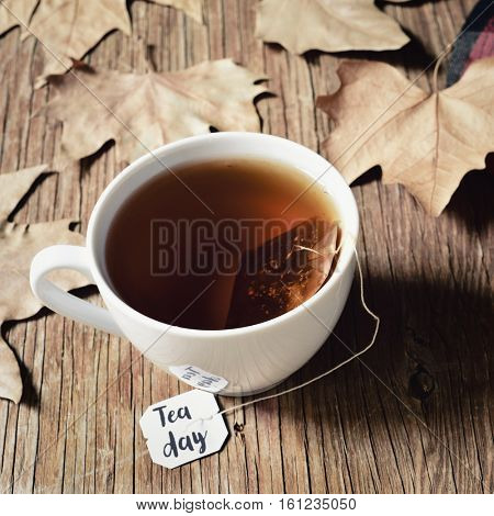 closeup of a white ceramic cup with a bag of tea being soaked in hot water, with the text tea day written in its label, on a rustic wooden table with some dry leaves