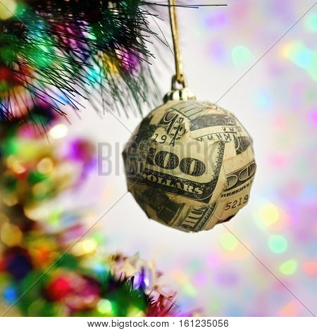 a christmas ball wrapped in pieces of a one hundred dollar banknote hanging from the branch of a christmas tree
