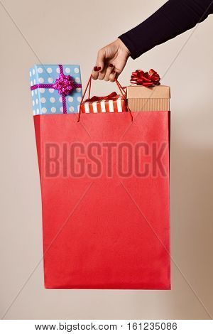 closeup of the hand of a young caucasian woman with her fingernails painted red holding a red shopping bag full of gifts wrapped in different papers, and a negative space in the bag
