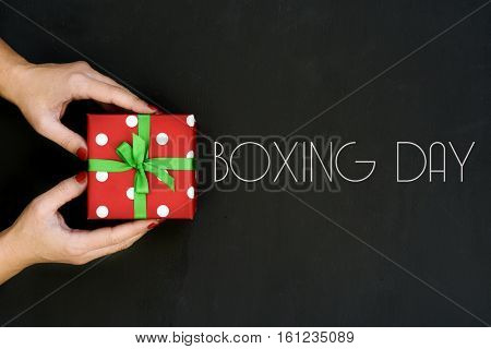 high-angle shot of a young caucasian woman with a gift in her hands wrapped in a red paper patterned with white dots and tied with a green ribbon, and text boxing day written on a dark gray surface