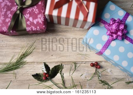 high-angle shot of some cozy gifts wrapped in different papers and tied with ribbons of different colors, and some natural ornaments, on a rustic wooden surface, with a negative space