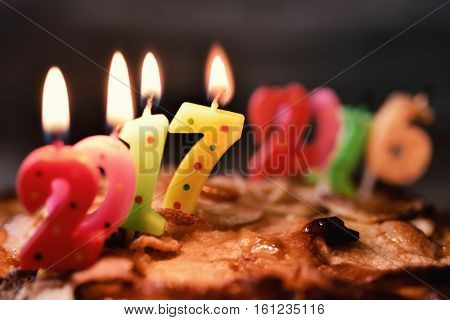 four lit number-shaped candles of different colors forming the number 2017, as the new year, on a cake, and more burn-out and melted candles forming the number 2016, as the old year, in the background