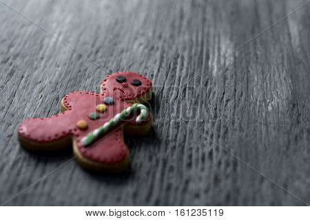 closeup of a sad gingerbread man on a rustic wooden surface, with a negative space
