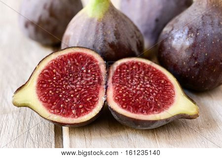 closeup of some appetizing ripe figs, one of them cut in half, on a wooden table