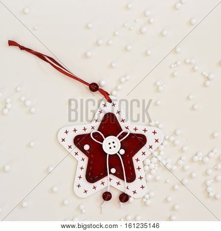 high-angle shot of a cozy handmade christmas ornament  placed on an off-white surface sprinkled with small plastic balls simulating snow