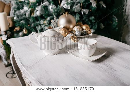 Christmas decorations on the table against the background of a fireplace decorated with branches of spruce and garland