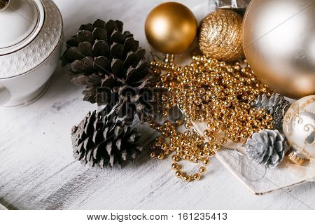 Different kinds cones, Christmas decorations and spruse branch on a wooden background.