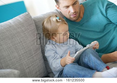 Daddy watching little girl using digital tablet