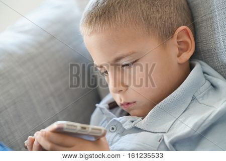 Closeup of 4-year-old boy playing with smartphone