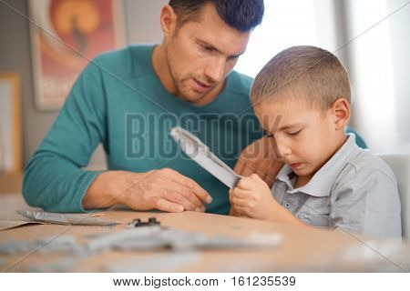 Father and son building up model together