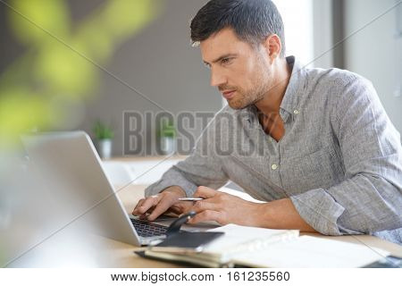 Middle-aged man working from home on laptop computer