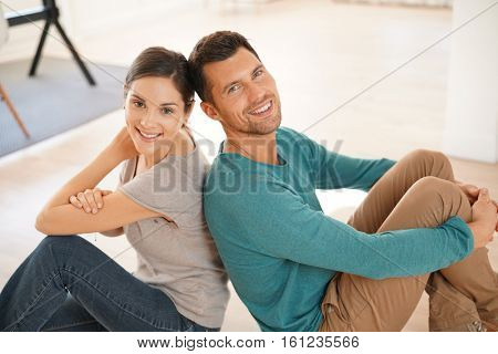 Cheerful couple sitting on floor at home