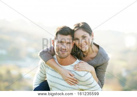 Portrait of cheerful man giving piggyback ride to girlfriend