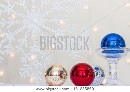 horizontal image of a large imitation snowflake in the background with blurred lights and red and gold and blue Christmas ball in the fore front.
