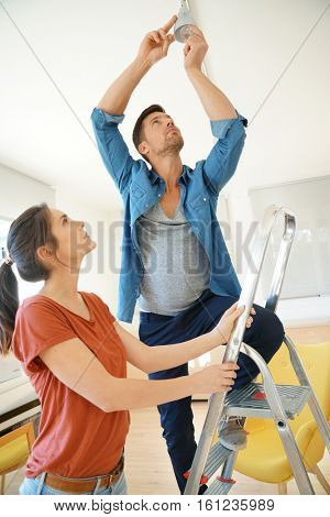 Couple in new home changing lamp bulb