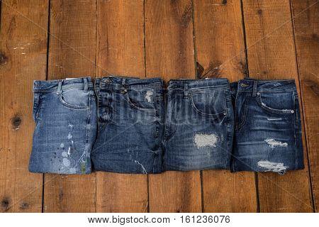 Four blue denim jean â??wooden background