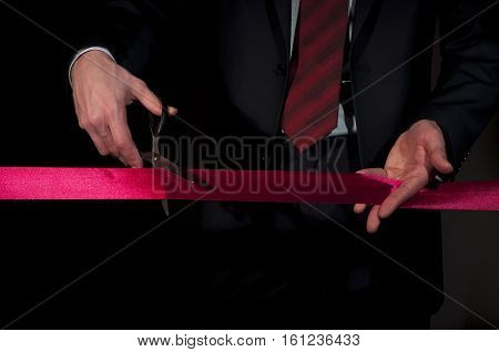 man in a suit, cuts a red tape, opening of event