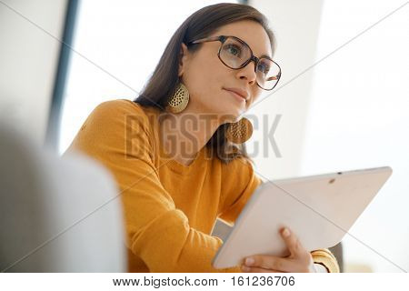 Portrait of trendy girl with eyeglasses websurfing on digital tablet