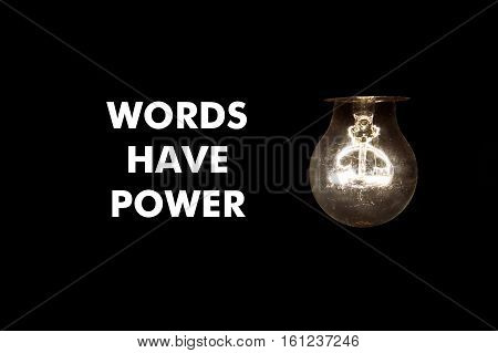 Bulb with message Words have power on black background