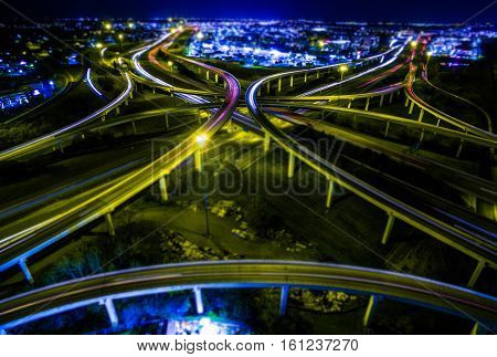 Tilt Shift Aerial Highway Interchange Loops and Turn arounds as the City lights grow at Night Speed of Light energizes on a new Road of Technology into the future