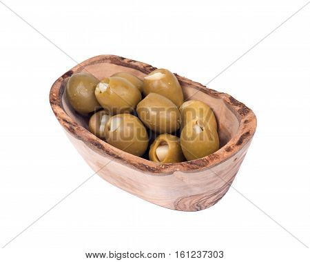 Green colossal olives hand stuffed with garlic gloves in olive wood bowl isolated on white background