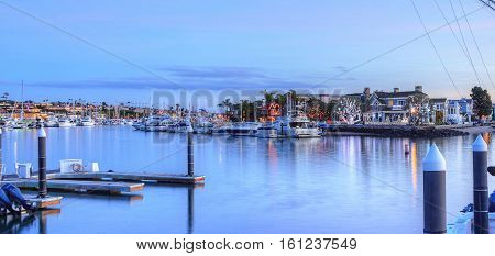 Christmas lights in Balboa Island harbor with ships and sailboats in front of decorated homes in Southern California, USA
