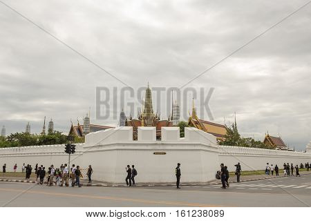 BANGKOK THAILAND - NOV 13 : people on corner of wat phra kaew at Ratchadamnoen Nai road in sanam luang area while the funeral of king Bhumibol Adulyadej in Grand Palace on november 13 2016