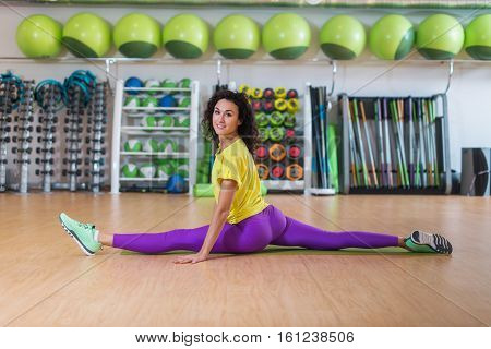 Pretty fitness model in sportswear doing front split in gym, stretching her legs, looking at camera and smiling