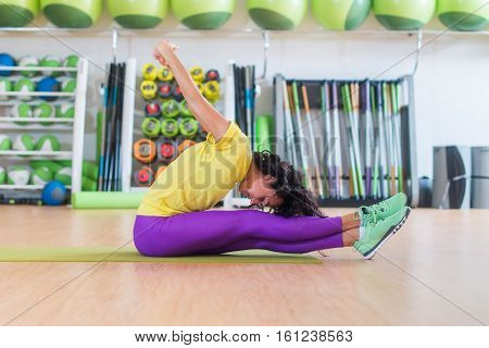 Side view of athletic female working out on mat in gym, bending and stretching her back and leg muscles.