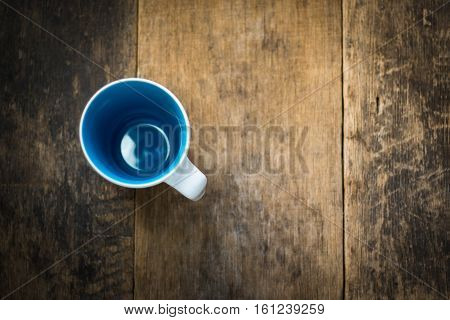 White Cup Inside Blue Colored On Wooden Background