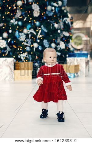 Portrait of happy Caucasian blonde baby girl toddler in red dress standing walking by New Year tree near gift boxes candid lifestyle image.