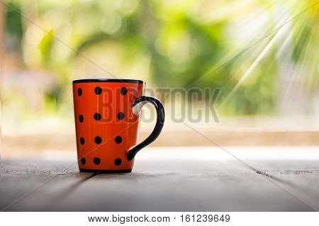 Spotted cup on wooden background with ray of light