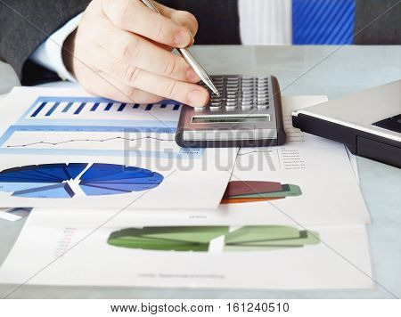 Closeup of male hand with pen using calculator on financial  charts